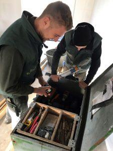 Paul en Danny ruimen hun materialen op